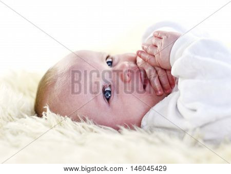 Cute little baby on a sheep fur. Baby smiling and looking into the camera. White bedroom with beautiful baby, close-up shot.