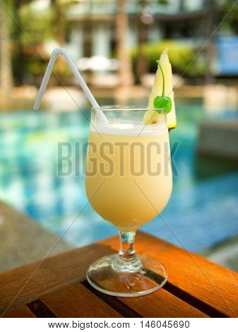 Pina Colada cocktail on a table on tropical island. Palm trees on background