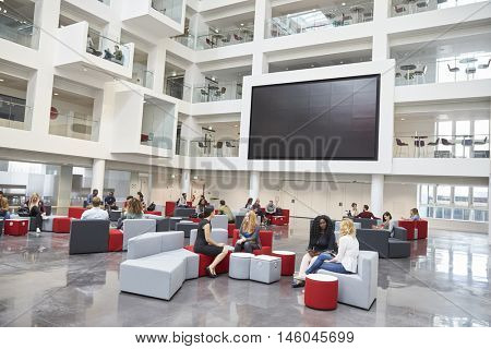 Students meeting in front of screen in atrium at university