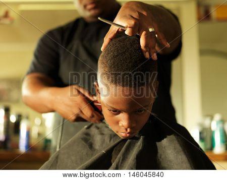 little boy getting hair cut by barber