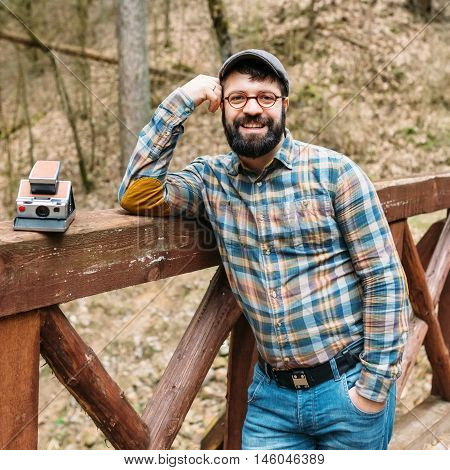 Portrait of a bright pleasant smiling male photographer with film cameras on a wooden bridge in a picturesque forest hipster life style trips
