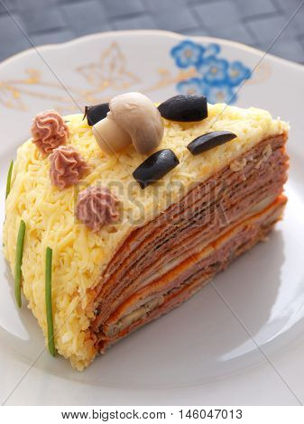 One piece of homemade salty pancake cake with ham mushrooms olives and mayonnaise
