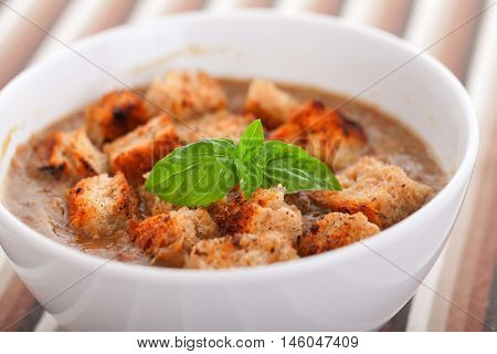 Italian lentil soup with fried bread croutons. Decorated with basil leaf.