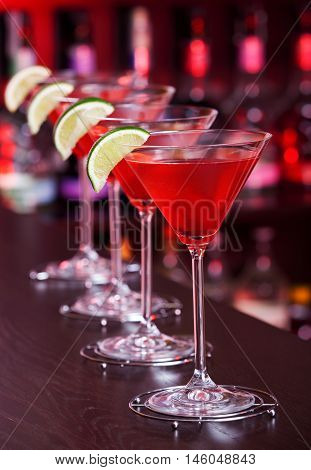 Row of Cosmopolitan cocktails shot on a bar counter in a nightclub. Low angle view