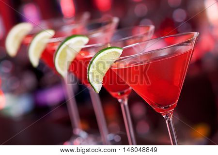 Row of Cosmopolitan cocktails shot on a bar counter in a nightclub. Low angle view tilted
