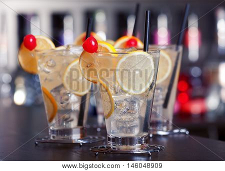 Four Tom Collins cocktails on a bar in a nightclub. Horizontal shot