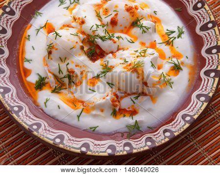 Poached eggs in white yogurt sauce. Horizontal shot.