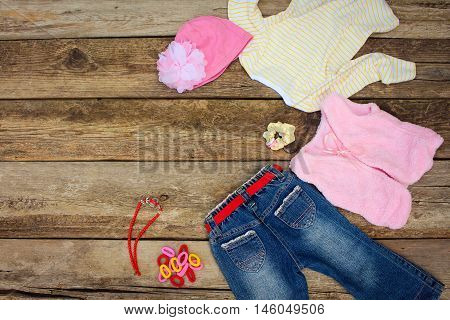 Girly clothing and accessories: jeans, blouse, hat, hair clips, beads and warm vest on old wooden background. Top view.