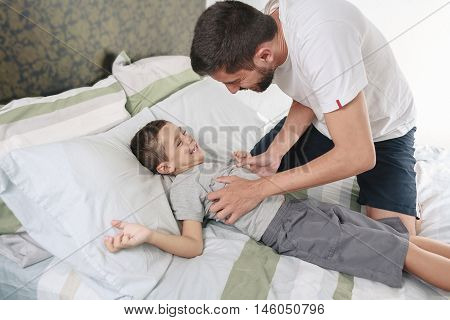 Father Tickling His Son On The Bed
