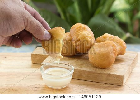 Hand hold deep fried dough bun dip in sweetened condensed milk
