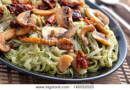 Italian Linguini pasta with pesto and mushrooms in a dark plate. Close up