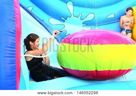teen girl and preteen boy in open air aqua park in water trampoline play water gun war game close up photo