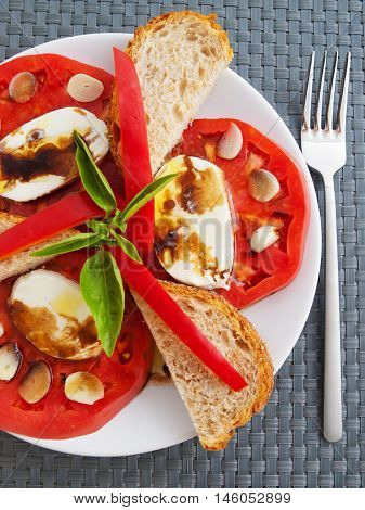 Caprese salad with toasts and balsamic vinegar. Shot from above