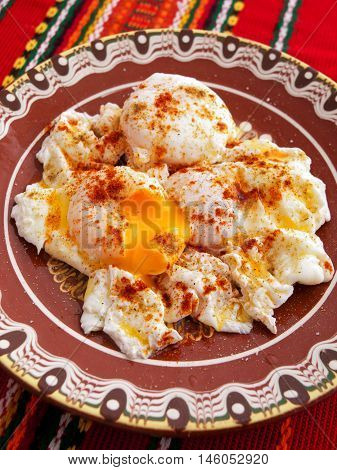 Poached eggs with red pepper. Vertical shot.