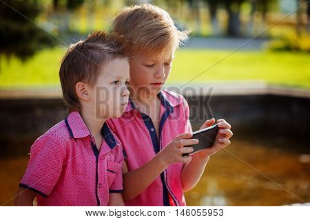 Two little boys playing games on mobile phone in sunny day