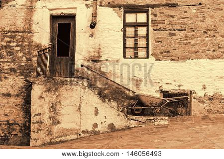 Old Stone House With Wooden Door and Window Staircase Rusty Gutter and Wheelbarrow in Sepia