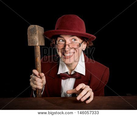 Strange person in a suit and bowler holding wooden hammer with unpleasant smile. Color toning