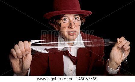 Strange person in a suit and bowler pulling duct tape threateningly. Color toning