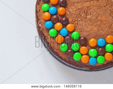 Birthday cake decorated with bright candies upon light background. Top view, selective focus on the top. Copy space for you text.