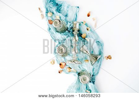 decorated composition with golden candlesticks dry autumn leaves and blue textile on white background. Flat lay top view