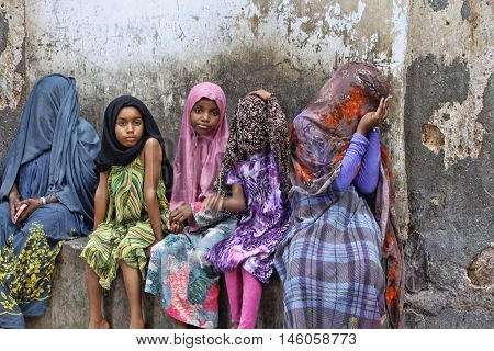 Stone Town Tanzania - January 10 2016: Children in traditional Muslim clothes sitting on the street of Stone Town.