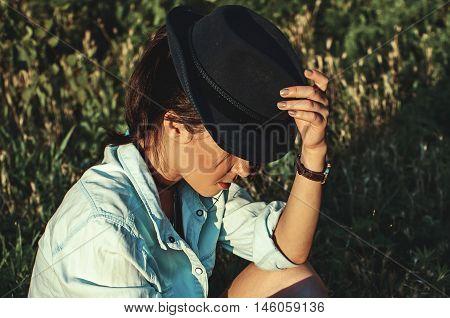 girl in black hat sitting in park