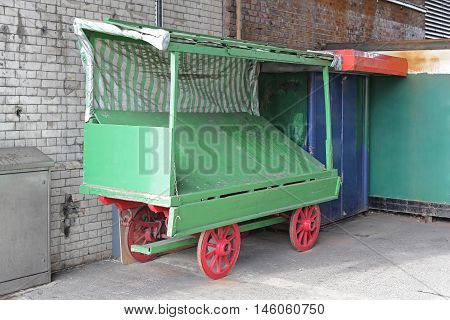 Empty Green Vendor Cart With Red Wheels