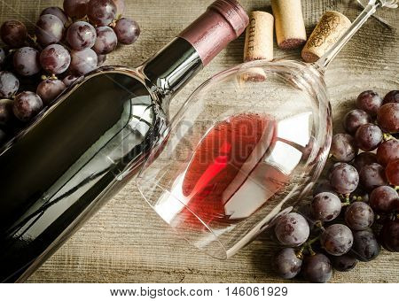 Red wine in a glass and bottle with grapes and corks