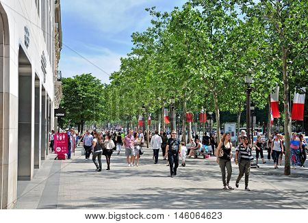 PARIS FRANCE - MAY 7: Undefined people walking by Champs Elysees street in Paris on May 7 2011. Champs Elysees is the main shopping street of Paris city France.