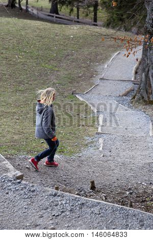 young girl is running down on a natural path