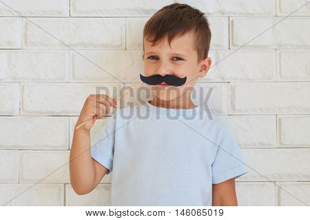 Young gentleman holding paper moustache with rather shrewd look standing against white wall