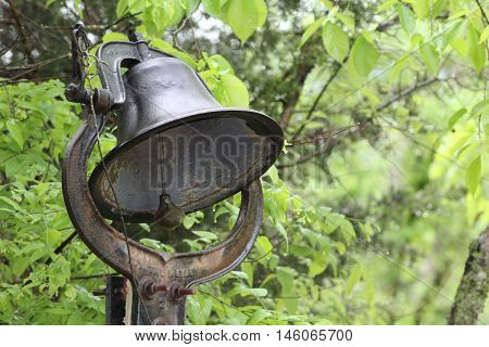 Rusty iron dinner bell against green forest