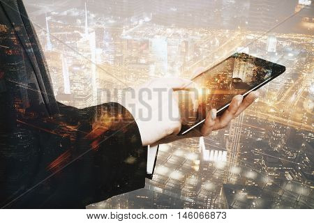 Close up and side view of male hands using tablet on city background. Double exposure