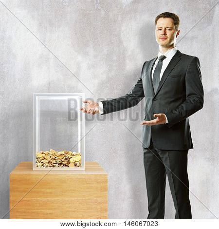 Young businessman in suit showing donation box on concrete background. 3D Rendering