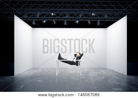 Relaxing businessman with feet on table against truss stage. 3D Rendering