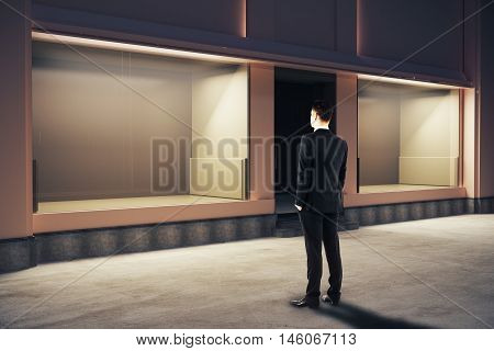 Confident businessman looking at empty clean storefront at night. Side view Mock up 3D Rendering