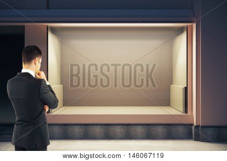 Thoughtful businessman looking at empty clean storefront at night. Mock up 3D Rendering