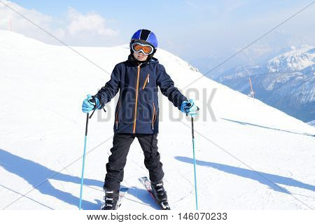 young boy is standing near a ski route