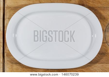 Flat white shallow porcelain oval plate with shoulders on wooden cutting board directly from above