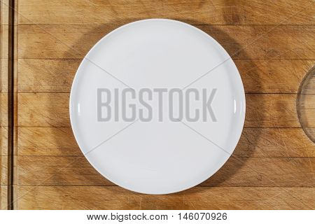 Flat white shallow porcelain plate on wooden cutting board directly from above