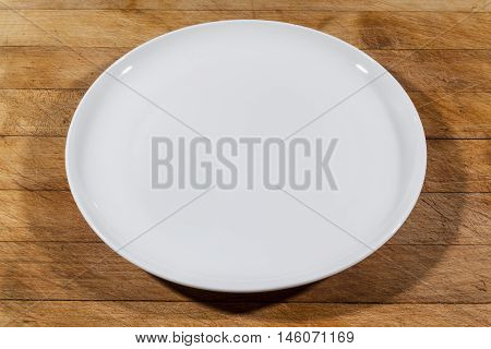 Flat white shallow porcelain plate on wooden cutting board from side