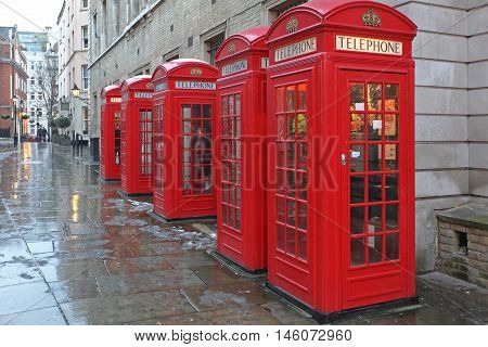 LONDON UNITED KINGDOM - JANUARY 19: Red Telephone Boxes in London on JANUARY 19 2013. Five Red Telephone Booths at West End in London United Kingdom.