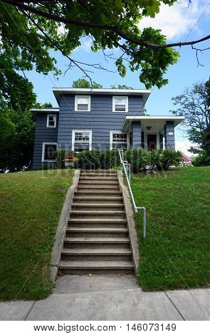 PETOSKEY, MICHIGAN / UNITED STATES - AUGUST 5, 2016: A concrete stairway leads to a blue home on Mitchell Street near downtown Petoskey.