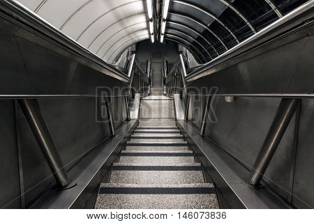 Stairwell descending to a dim and gloomy underground tunnel