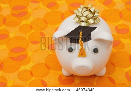 Saving Money for Education A white piggy bank with grad hat on orange circle background