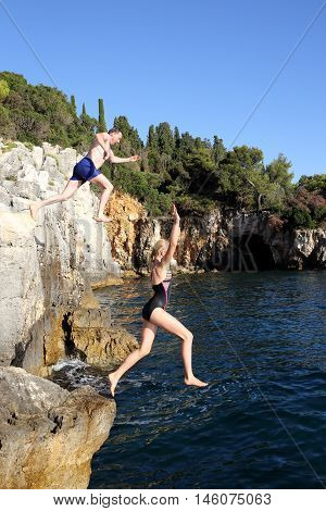 two people are jumping from a cliff