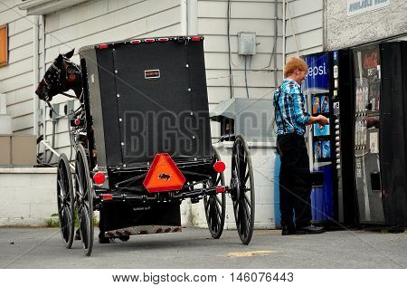 Intercourse Pennsylvania - June 7 2015: Amish youth and his parked horse and buggy stops to buy a Pepsi Cola from an outdoor vending machine