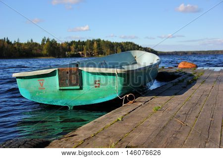 near a wooden dock, pier, tethered old boat light green at number five, deep blue lake water, blue sky with clouds, forest