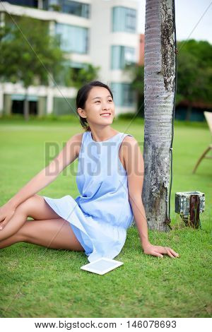 Asian girl sitting on grass with a reading device