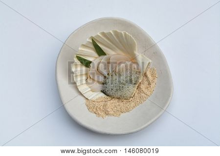shellfish clams with sea foam reduction on sand made of bread